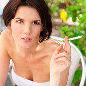 Portrait of a beautiful woman smokes a cigarette outdoor at cafe — Stock Photo