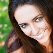 フォレスト内の芝生の上に座っている笑顔若い女の子の肖像画、 — ストック写真