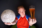 Portrait of young man watching tv translation of football game with his favourite team and holding ball and drinking beer — Stock Photo