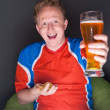Portrait of young man watching tv translation of football game with his favourite team and drinking beer — Stock Photo