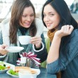 Two beautiful women having lunch and chatting at cafe — Stock Photo #9730838