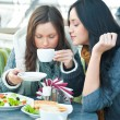Two beautiful women having lunch and chatting at cafe — Stock Photo #9730915