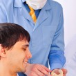 A young male patient in a dentist office looking at plaster cast of his teeth — Stock Photo
