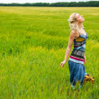 Stock Photo: Candid carefree adorable womin field with at summer sunset wearing bright colorful dress
