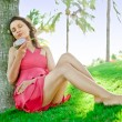 Portrait of young pretty woman wearing bright pink dress eating exotic asian dragon fruit and enjoying her vacation at tropical resort - Foto Stock
