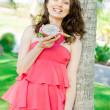 Vacation woman enjoying exotic fruit in tropical resort. Gorgeous Caucasian young woman in elegant pink dress during summer holidays. - Foto Stock