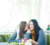 Two beautiful women drinking coffee, having lunch and chatting at cafe — Stock Photo