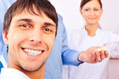 Portrait of happy smiling male patient and doctor with his assistant at office. Focus on man. — Stock Photo
