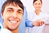 Retrato de paciente masculino sonriente feliz y doctor con su asistente en la oficina. centrarse en el hombre. — Foto de Stock