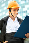 Young architect-woman wearing a protective helmet standing on the building background — Stock Photo