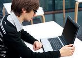 Amigável executivo sentado na frente do laptop em seu escritório. — Fotografia Stock
