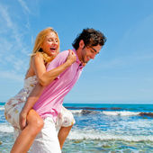 An attractive couple fooling around on the beach — Foto Stock