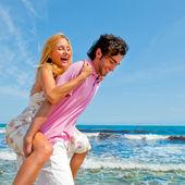 Um casal atraente, brincando na praia — Foto Stock