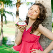 Portrait of young pretty woman wearing bright pink dress eating exotic asian dragon fruit and enjoying her vacation at tropical resort — Stock Photo