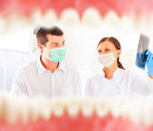 A dentist and a nurse preparing to cure patient. — Stock Photo