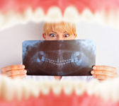 Mouth with teeth from inside and dentist holding x-ray results and very surprised — Stock Photo