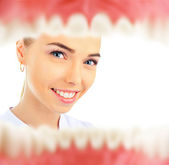 Pretty young female dentist looking inside patient's mouth view from inside — Stock Photo