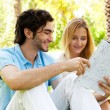 Happy couple of students with a notebook sitting on grass at cam — Stock Photo #9931721