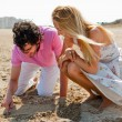 Couple in love drawing a heart in the sand while relaxing at bea — Foto Stock