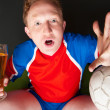 Young man holding soccer ball and beer and watching tv translati — Stock Photo #9932338