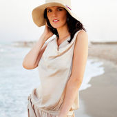 Smiling young woman wearing a straw hat and having fun at the be — Stock Photo