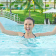 Woman in a pool having fun with splash — Stock Photo