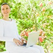 Young pretty woman with laptop sitting on the bench in a park — Stock Photo #9982633