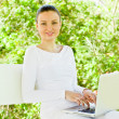 Young pretty woman with laptop sitting on the bench in a park — Stock Photo #9982646