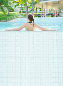 A beautiful woman sunbathing by the pool. Photo from behind her back. Lots of copyspace — Stock Photo
