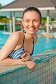 Prety young woman having fun at pool. Leaning on pool's side — Stock Photo