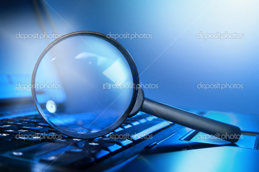 Magnifying lens on the laptop keyboard in blue light  Stock Photo #10525934