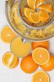 Fresh squeezed orange juice, juicer and oranges with white background. — Stock Photo