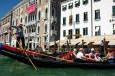 Venetian gondola with tourists, sunny summer day in Venice — Stock Photo