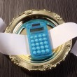 Calculator and blank paper on a golden plate - Stock Photo