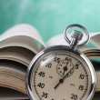 Stock Photo: Stop watch in front of book