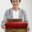 Young man carrying stack of gifts, smiling, portrait — Stock Photo #8017749