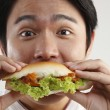 Man eating burger on the white background — Photo