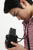 Side view of man holding antique camera — Stock Photo