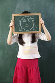 Girl holding black board with drawing — Stock Photo