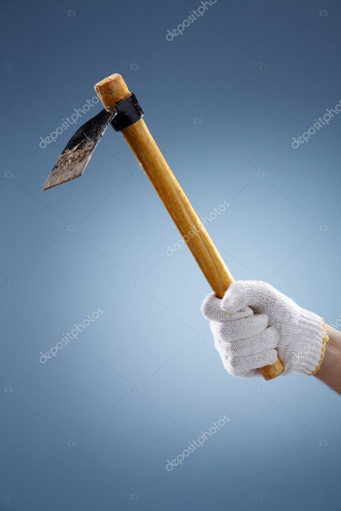 Hand holding garden trowel on coloured background. — Stock Photo #8276848