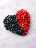 Rojo y negro colorean forma de bombones en forma de un corazón — Foto de Stock