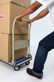 Delivery man pushing a trolley with boxes — Stock Photo