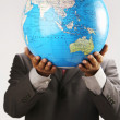 Businessman holding globe over face — Stock Photo