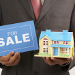 Real estate agent holding a sign of for sale and a model house — Stock Photo