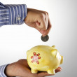 Stock Photo: Man saving money in the piggy bank