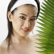 Young woman wearing towel, holding green leaf — Stock Photo #9188097