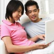 Couple surfing the internet together in the living room — Stock Photo