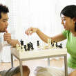 Couple playing chess at home - ストック写真