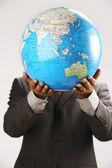 Businessman holding globe over face — Stock Photo