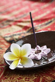 Burning incense placed in the plate on batik background — Stock Photo